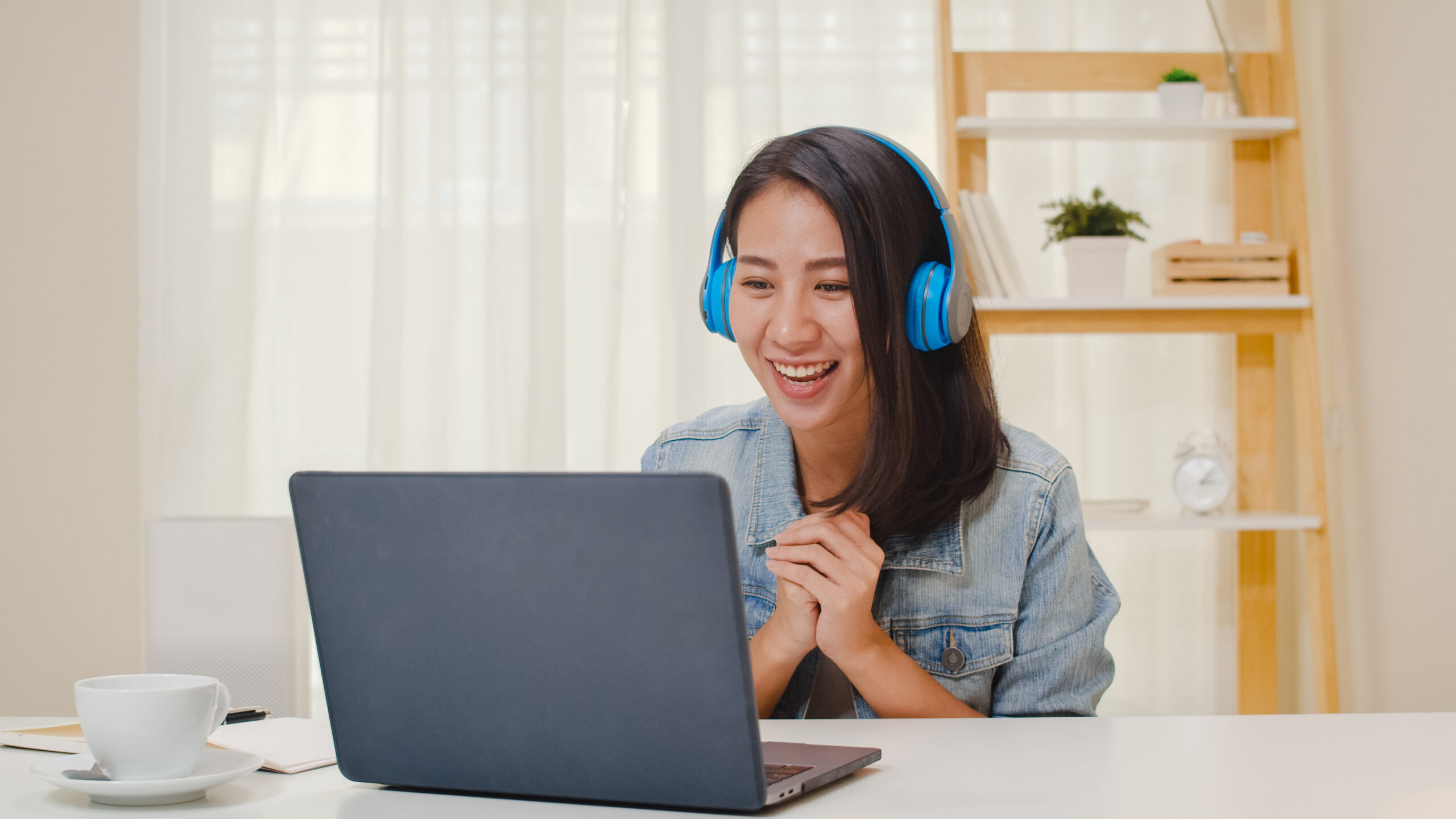 Freelance business women casual wear using laptop working call video conference with customer in workplace in living room at home. Happy young Asian girl relax sitting on desk do job in internet.